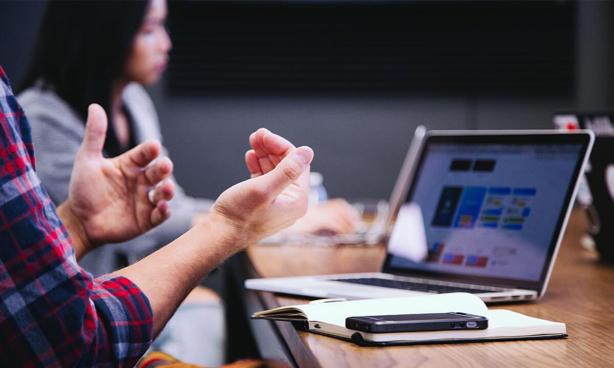 Sfeerbeeld van mensen die achter een bureau aan het werk en overleggen zijn met opengeklapte laptops