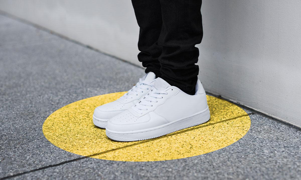 Close up van twee witte sneakers die op een gele stip op straat staan.