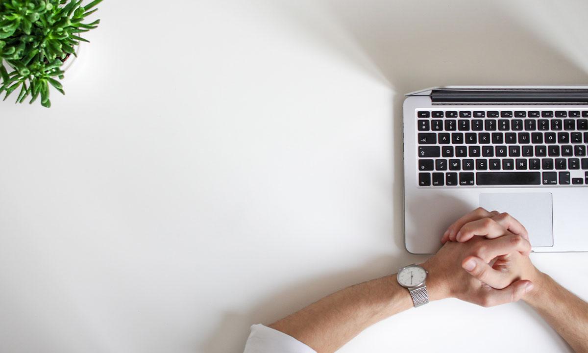 Sfeerafbeelding van een wit bureau met gevouwen handen voor een toetsenbord en een plant