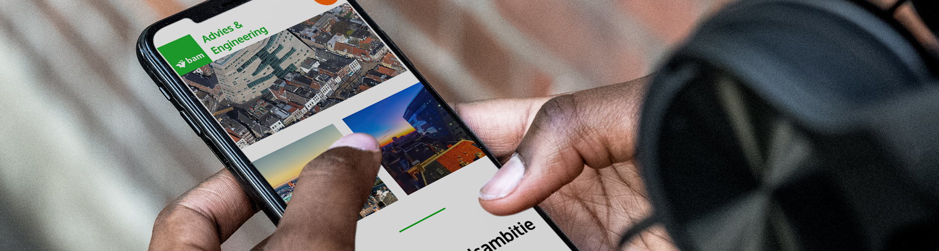 Man heeft een iPhone in zijn handen met daarop de website van bam