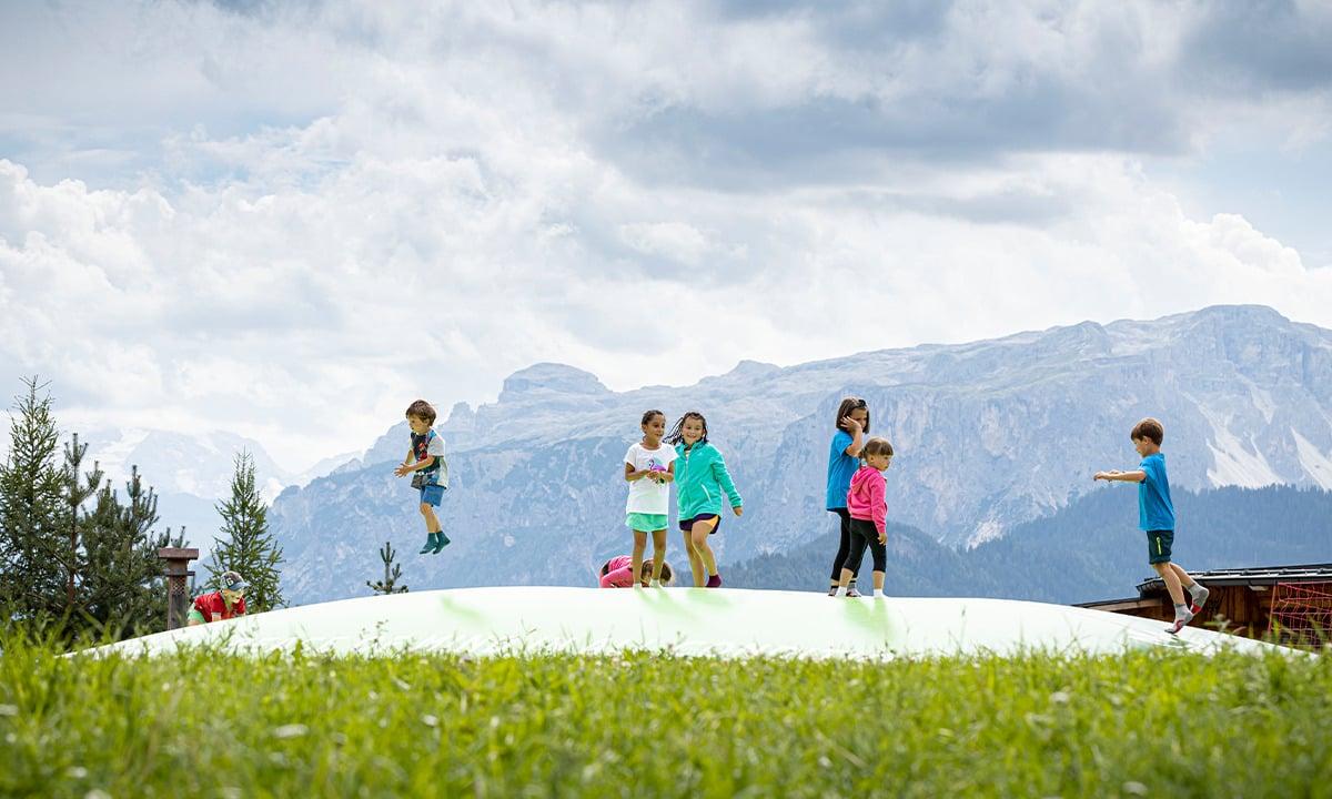 Afbeelding van een airmountain springkussen midden op een berg met spelende kinderen