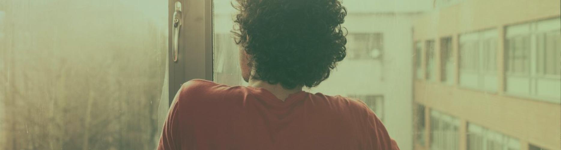 Sfeerafbeelding van een man die naar buiten staat te staren