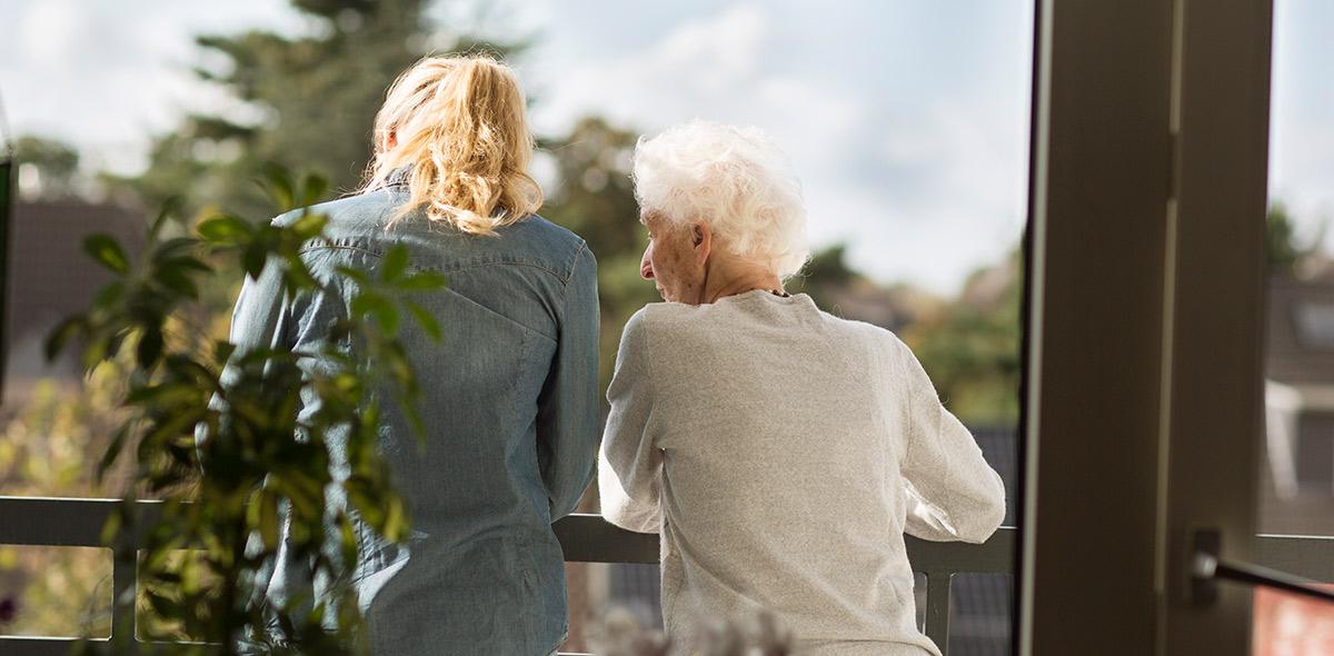 Afbeelding van een oudere vrouw die met haar dochter op het balkon staat naar buiten te kijken