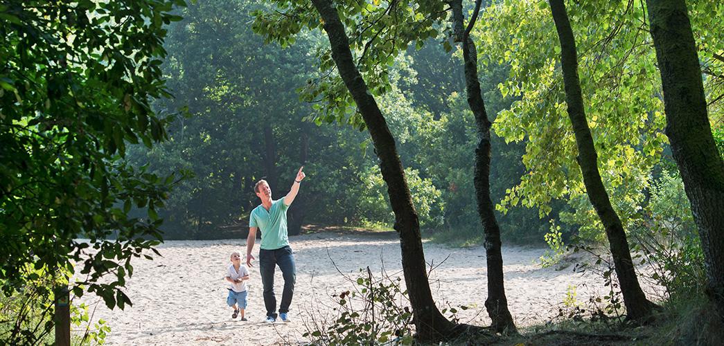 Sfeerafbeelding van een vader die met zijn dochter over een zandvlakte loopt