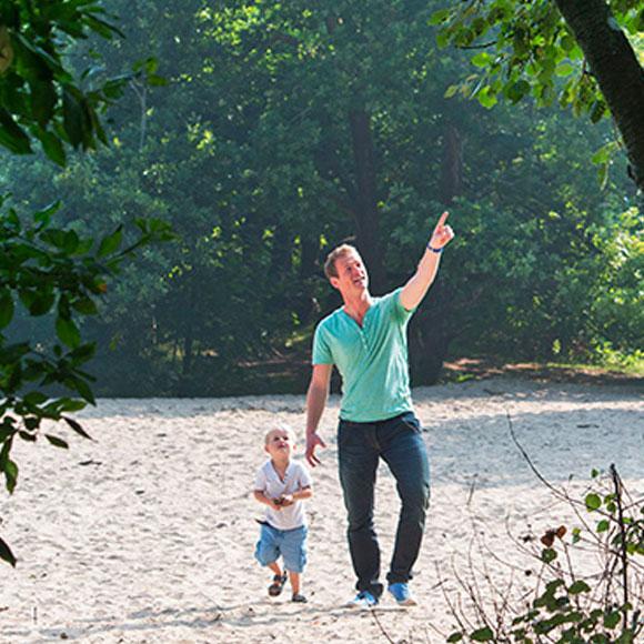 Sfeerbeeld van een vader die met een klein kind wandelt in de natuur