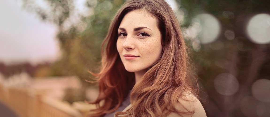 Sfeerafbeelding van een vrouw in de natur die naar de fotograaf kijkt