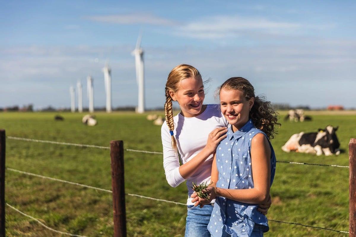 Foto van twee jonge meisjes voor een wei met koeien