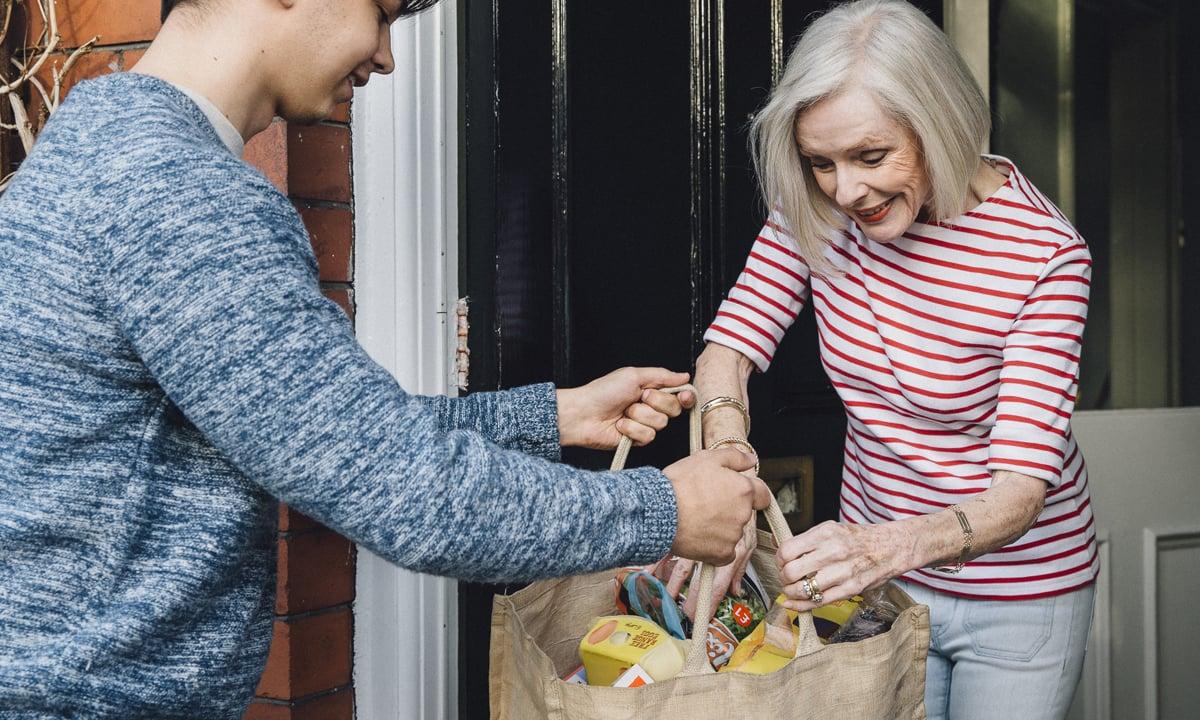 Foto van een jongen die boodschappen bezorgt bij een oudere vrouw