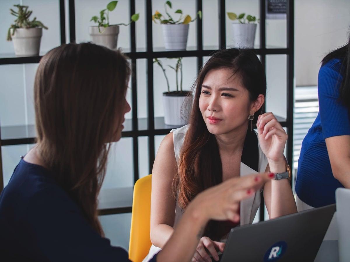 Sfeerbeeld van vrouwen die achter een bureau aan het werk zijn en overleggen zijn met opengeklapte laptops